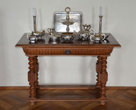 Antique table for serving with silver utensils Royalty Free Stock Photos