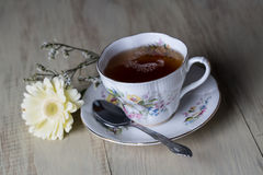 Antique Tea Cup Full of Tea with Yellow Daisy Flower Stock Photos