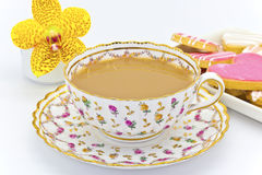 Antique tea cup with tea and biscuits. Royalty Free Stock Image
