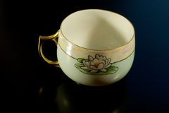 Antique teacup. A beautiful antique teacup on a black background royalty free stock photography