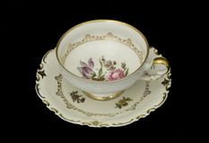 Antique teacup. Antique gold-rimmed floral china teacup and saucer. Isolated on black Royalty Free Stock Photo