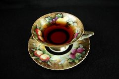 Antique teacup on black. Vintage teacup with tea isolated on black royalty free stock image