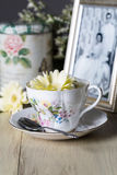 Antique Teacup With Old Framed Photograph and Yellow Daisies Stock Photo