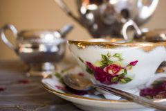 Antique teacup and silver tea set. Antique teacup decorated with red flowers on matching saucer with silver spoon in front of antique sterling silver tea set royalty free stock image