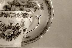 Antique teacup on white. Antique teacup sepia color royalty free stock photography