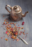 Antique teapot and strawberry tea on dark wooden background Royalty Free Stock Photography