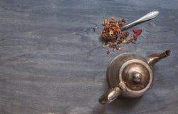 Antique teapot and strawberry tea on dark wooden background Stock Photos
