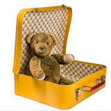 Antique Teddy bear sitting in a yellow suitcase wants to travel Stock Image