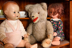 Antique teddy with dolls sitting in a cabinet Stock Photos