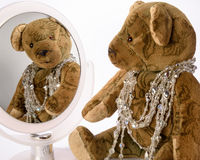 Antique Teddy has adorned herself with jewelry chains and is loo. King at herself in the mirror Royalty Free Stock Images