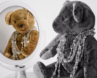 Antique Teddy has adorned herself with jewelry chains and is loo. King at herself in the mirror Stock Images