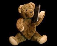 Antique Teddy phoning with a modern smartphone. Black bachground Stock Photography