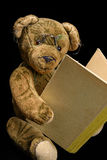 Antique Teddy reading in an old book. An antique Teddy with glasses is reading in an old book Stock Image