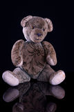 Antique Teddy on reflective black base. Antique Teddy sitting on reflective black base Royalty Free Stock Images
