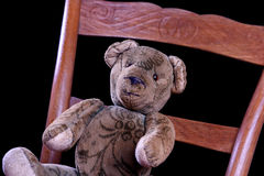 Antique Teddy sitting on an antique chair. Antique Teddy is sitting on an antique chair Stock Photos