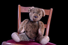 Antique Teddy sitting on an antique chair. Antique Teddy is sitting on an antique chair Royalty Free Stock Photography