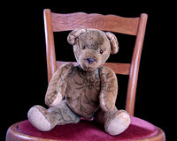 Antique Teddy sitting on an antique chair. With red velvet Royalty Free Stock Images