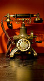 Antique telephone. Beautiful decorated antique telephone on an expensive antique table Royalty Free Stock Image