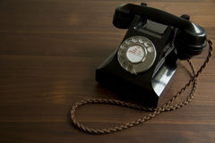 Antique telephone. Black antique telephone on desk Royalty Free Stock Photo