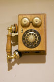 Antique Telephone. An antique telephone hanging on a wall Stock Photos