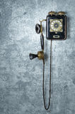 Antique telephone on a  blue wall. Antique telephone on a grungy blue wall Royalty Free Stock Images