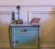 Antique Telephone on an Old Bedside Table Royalty Free Stock Images