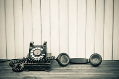 Antique telephone. With receiver off cradle or hook, wooden background Royalty Free Stock Photos