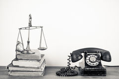Antique telephone and weighing scales. Black and white view of antique telephone and weighing scale on pile of books, white background Stock Photos