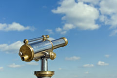 Antique telescope. Coin operated antique telesecope with brass and metal elements in front of a blue cloudy sky Royalty Free Stock Photos