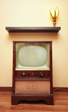 Antique Television. A retro TV sits below a shelf and a tulip lamp Royalty Free Stock Photo