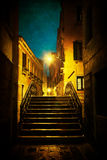Antique textured picture of a bridge in Venice at night Stock Photo