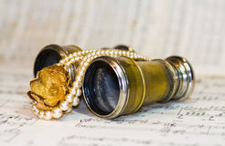 Antique theater binoculars over old music notes Stock Photo