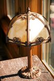Antique Tiffany Stlye Lamp. An antique Tiffany style lamp sitting on a marble top table in front of a window stock photos