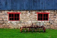 Antique tiller beside a barn Royalty Free Stock Photography