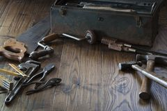 Antique tools and toolbox on dark wood surface royalty free stock photography