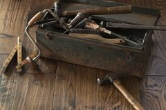 Antique tools and toolbox on dark wood surface stock photo