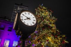 An antique Town Square clock stands in front of a beautiful, tall Christmas tree stock images