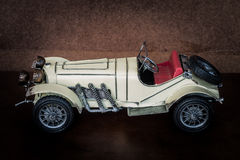 Antique toy car. On brown leather cushion Royalty Free Stock Photo