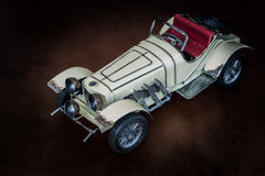 Antique toy car. On brown leather cushion Stock Images