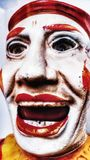 Antique Toy Clown Face. Scary, white, creepy, halloween, red, lips, laugh, joker, laughing, doll, figure, mask stock image