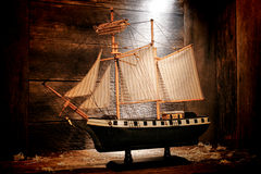 Antique Toy Model Sail Ship in Old Wood Attic. Antique wooden miniature toy reproduction model war navy sail ship with nostalgic aged canvas sails in an old wood Stock Images