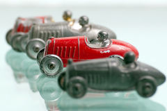 Antique toy race cars. Four antique toy race cars from the 1920's, lined up with the focus on one red racer. Each race car has a driver and are colored either Stock Photos