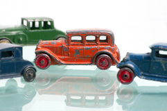Antique toy sedan cars. Four antique toy sedan cars from the 1920's, lined up with the focus on one orange sedan with red wheels.  The cars are orange, blue, and Royalty Free Stock Photos