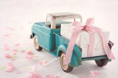 Antique toy truck carrying a gift box with pink ribbon. Old antique toy truck carrying a gift box with pink ribbon on romantic lace background and flower petals Stock Images