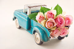 Antique toy truck carrying pink roses. Old antique toy truck carrying pink rose flowers Royalty Free Stock Photos