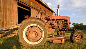 Antique Tractor. Antique red tractor in front of a faded red barn, on the farm at sunset Stock Images