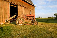 Antique Tractor. Antique red tractor in front of a faded red barn, on the farm at sunset Royalty Free Stock Photo