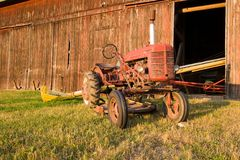 Antique Tractor. Antique red tractor in front of a faded red barn, on the farm at sunset Stock Photo