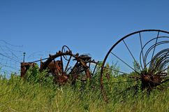 Antique Tractor and Dump Rake. An extremely old tractor and dump rake are parked in a field of long grass and weeds Royalty Free Stock Image