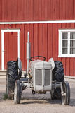 Antique tractor and old red farm facade. Agriculture rural farmi Stock Photography